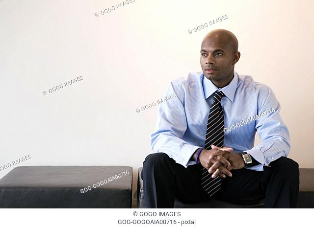 African businessman sitting on bench
