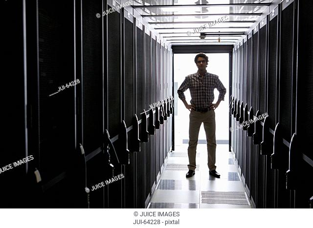 Technician standing in aisle of storage cabinets in data center