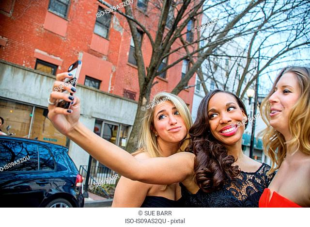 Three glamorous young adult female friends taking smartphone selfie on street
