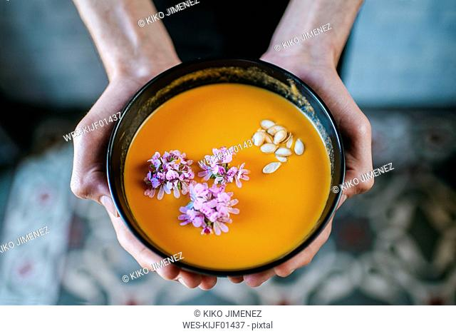 Man's hands holding creamed pumpkin soup garnished with edible flowers, close-up
