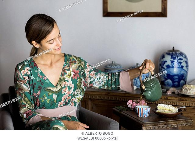 Young woman sitting in an armchair at home pouring tea into a cup