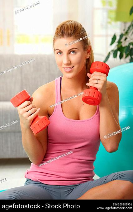 Young woman doing exercises with barbells in hand, smiling
