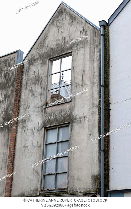 Empty window of ruined building facade revealing slate rooftops behind in old Amiens, France