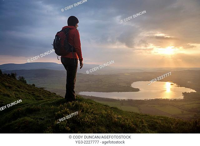 Female hiker takes in view of Llangorse lake from Mynydd Llangorse, Brecon Beacons national park, Wales