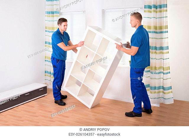 Young male movers carrying shelf at home