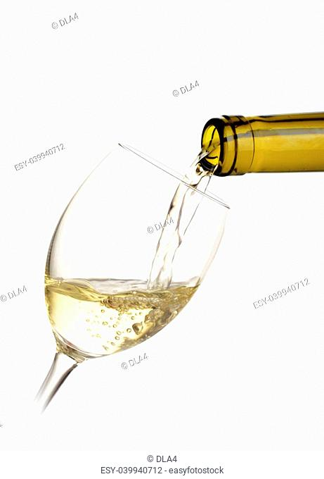 White wine poured into a glass on white background