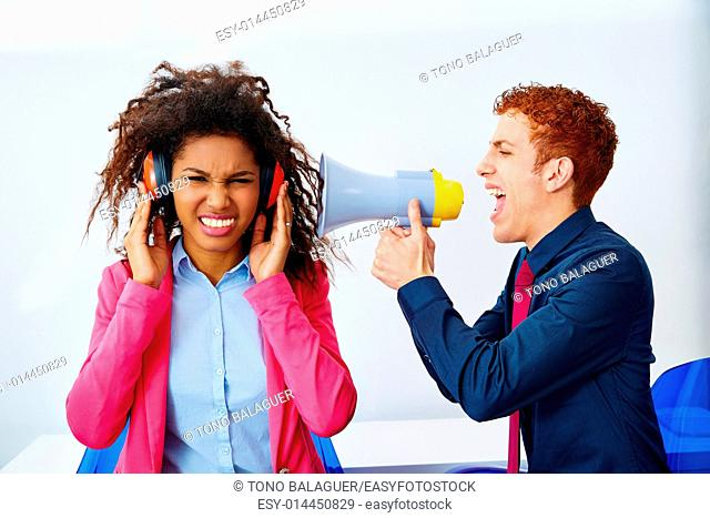 businessman shouting in megaphone to african executive with scared expression