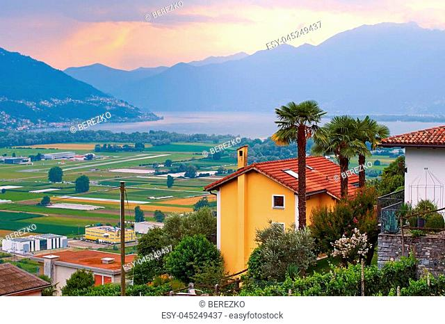 Evening view of rural Southern Switzerland with houses, farms, vineyards, alps mountains and Lake Maggiore