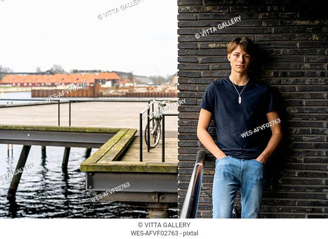 Denmark, Copenhagen, portrait of young man leaning standing at a wall at the waterfront
