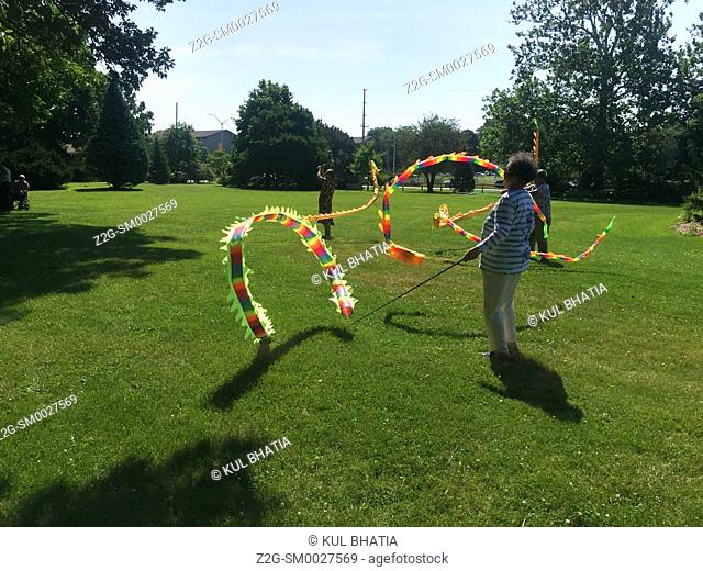 Women playing with Chinese kites in a green, urban park, Ontario, Canada. One twirls around one or two kites to create colorful waves