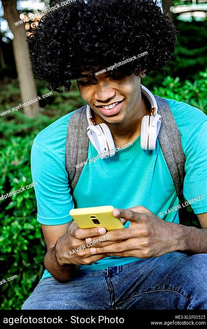 Smiling young man text messaging on smart phone while sitting in public park