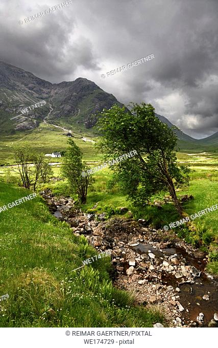 Stream to River Coupall valley with white cottage at foot of Buachaille Etive Mor mountains Glen Coe under dark clouds Scotland UK
