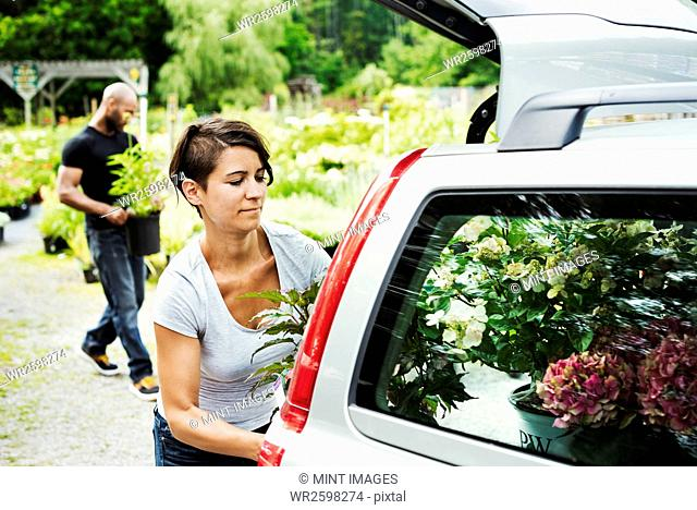 Car parked at a garden centre, a woman loading flowers into the boot