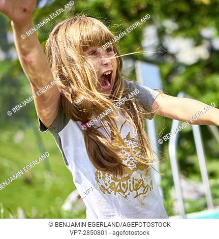 Happy young female child going wild in nature and screeming out loud