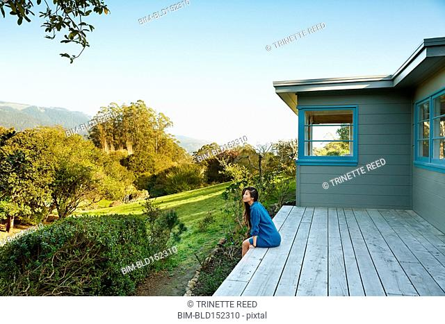 Chinese woman sitting on back porch