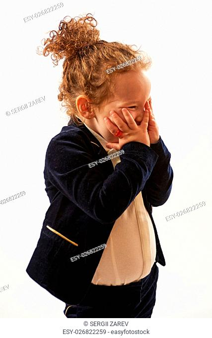 Little girl in black suit standing and pouting