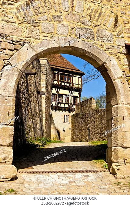 Looking through an archway in the wall of Bebenhausen Abbey, a historic monastery compound near Tubingen, Wurttemberg, Germany