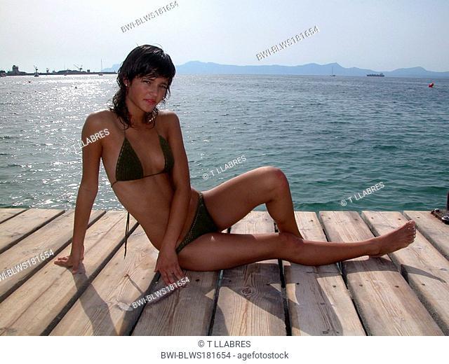 cute young, slim girl in bikini, sitting on a boardwalk at the sea, Spain, Balearen, Majorca