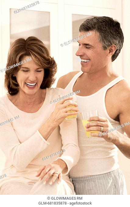 Couple drinking juice and romancing in the kitchen