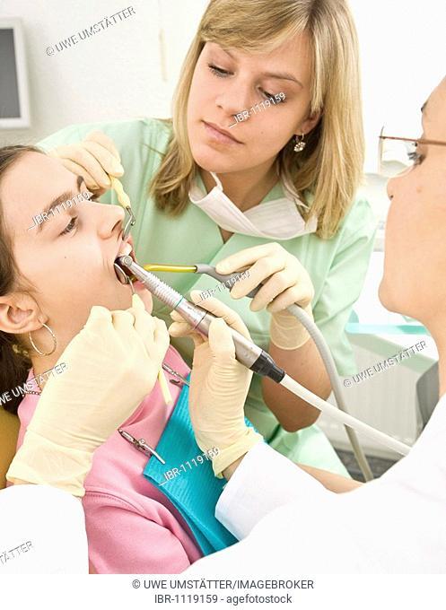 Dentist and nurse treating a girl