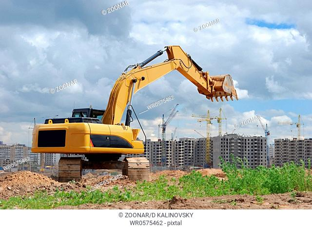 Excavator against microdistrict under constracion