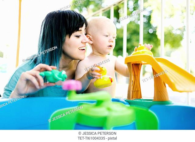 Mother with baby boy (12-17 months) playing with inflatable toys