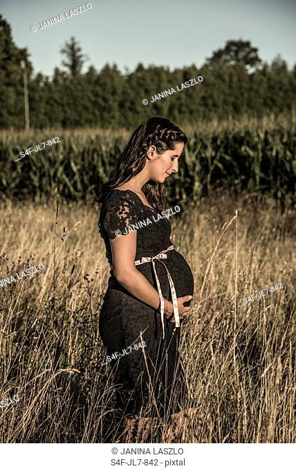 Schwangere Frau steht auf einem Feld