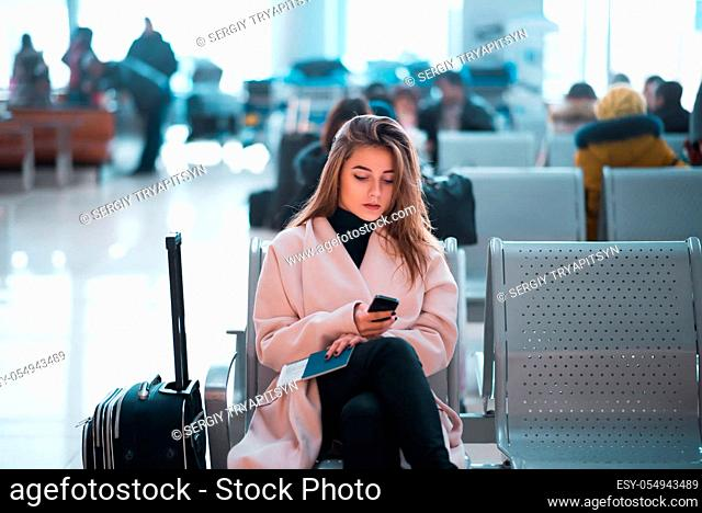 Airport business woman waiting in terminal. Air travel concept with casual businesswoman sitting with suitcase. Mixed race female professions