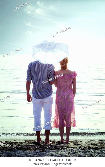 a couple on the beach with a parasol