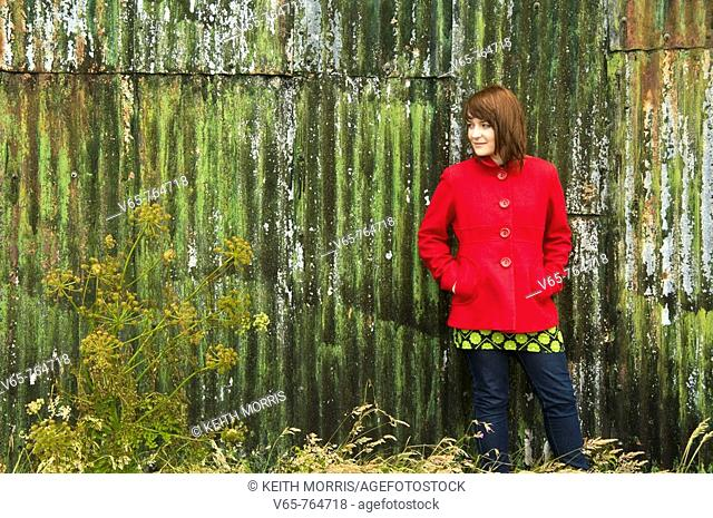 Teenage girl wearing red coat standing in front of green painted corrugated iron shed