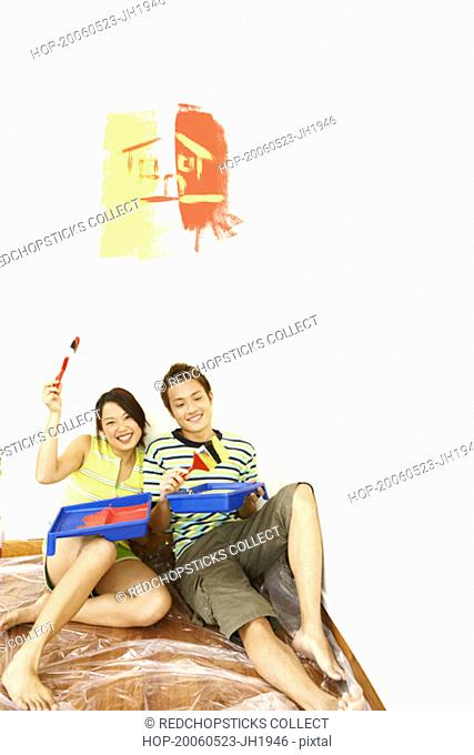 Portrait of a young couple holding paintbrushes and smiling