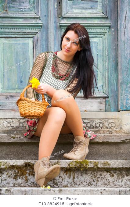 Countrygirl sitting on stairs with flowers in basket