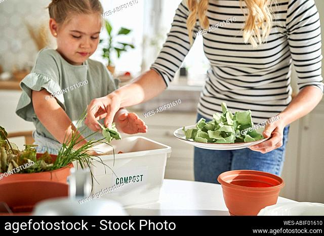 Mother and daughter making compost at home