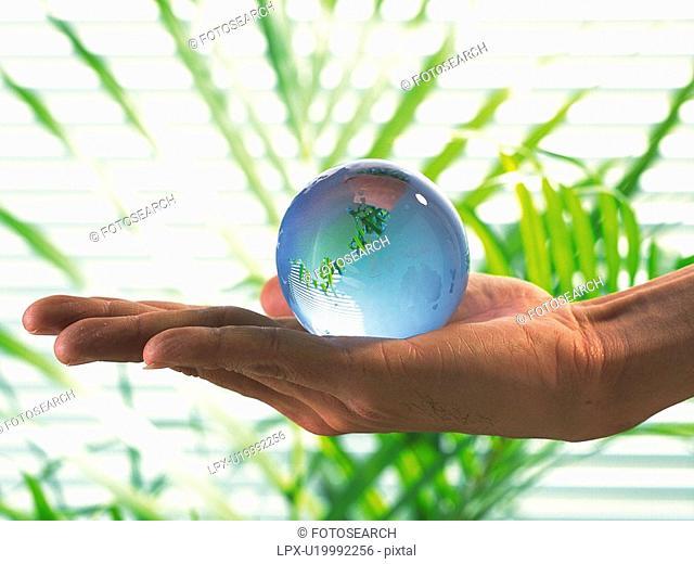 Hand holding a glass made globe, Close Up