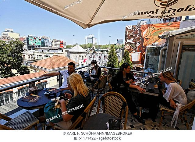 Young people on the roof terrace of a cafe, overlooking the Taksim Square, Istiklal Caddesi, Beyoglu, Istanbul, Turkey