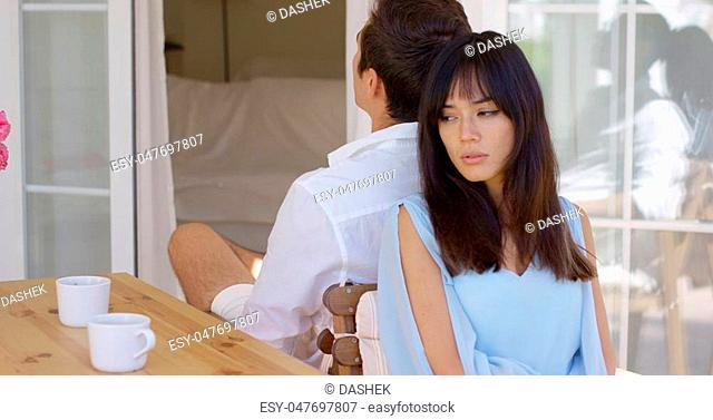 Angry mixed race couple ignoring each other after an argument sitting back to back on an outdoor patio with a sad expression