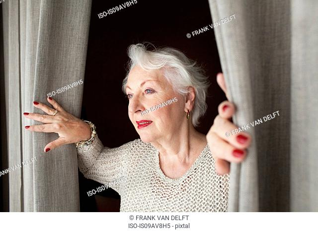 Senior woman, opening curtains