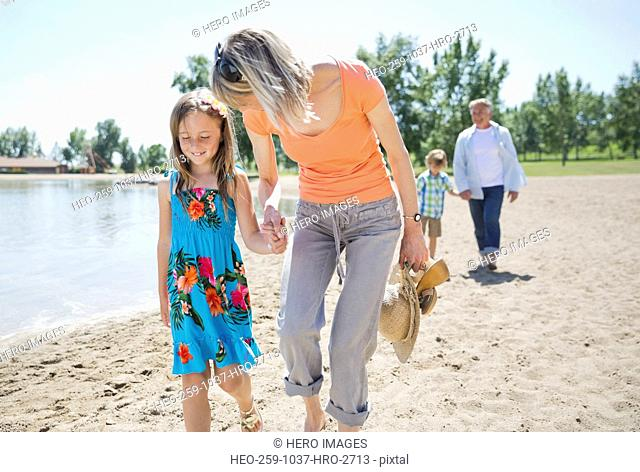 Little girl and grandmother walking on beach
