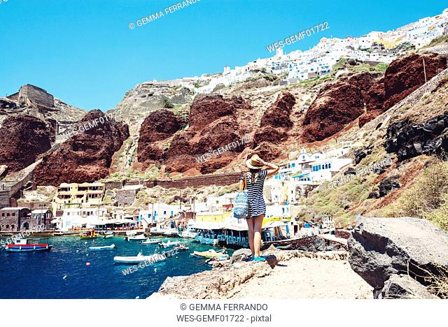 Greece, Santorini, Oia, woman enjoying the view in the fishing harbor with the white village above the cliff