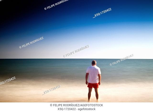 Man on a beach staring at the sea  Daylight long exposure shot by the use of neutral density filters  Model release available
