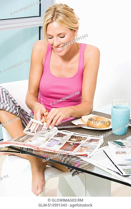 Mid adult woman cutting the newspaper with scissors and smiling