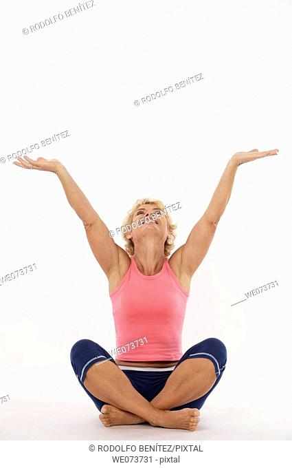 Woman in her 60s stretches and raises her open arms towards the sky in a studio setting