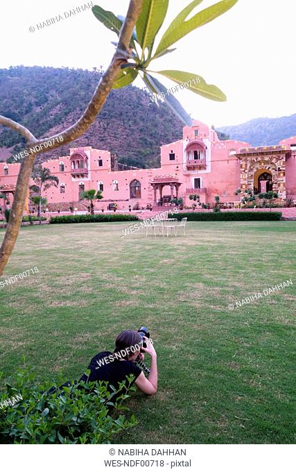 India, Rajasthan, Alwar, female tourist photographing Heritage Hotel Ram Bihari Palace