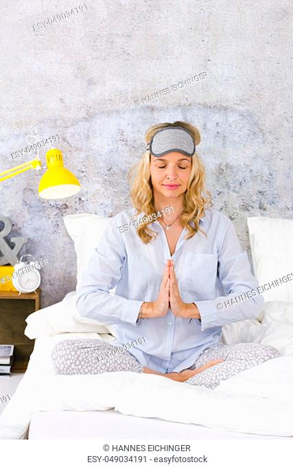 beautiful blond and young woman sitting in bed and doing yoga exercises in the morning