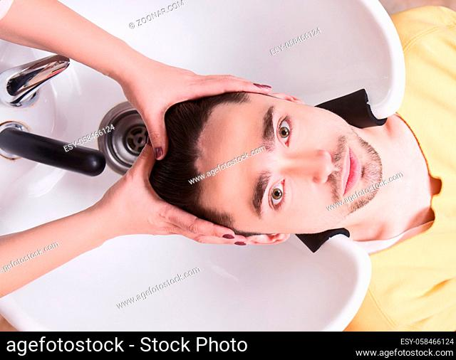 Topview picture of handsome man having his hair washed in hairdressing saloon. Young man lying with his eyes opened andlooking at camera in beauty saloon