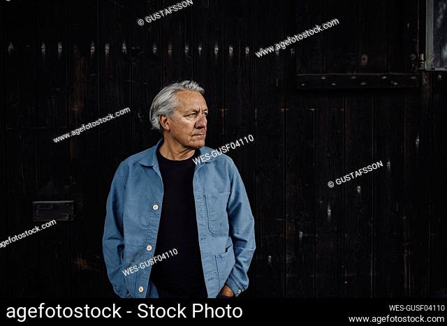 Senior man standing at wooden wall looking sideways