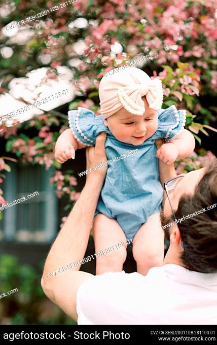 Little baby girl being held by her father