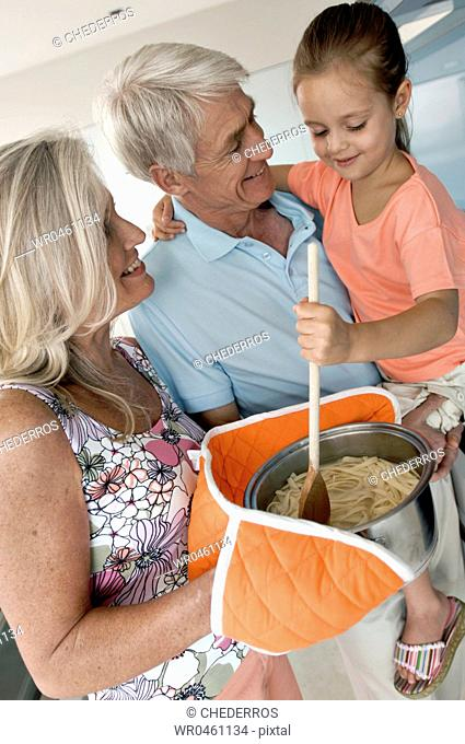 Close-up of a senior man carrying his granddaughter with a senior woman holding spaghetti in a saucepan