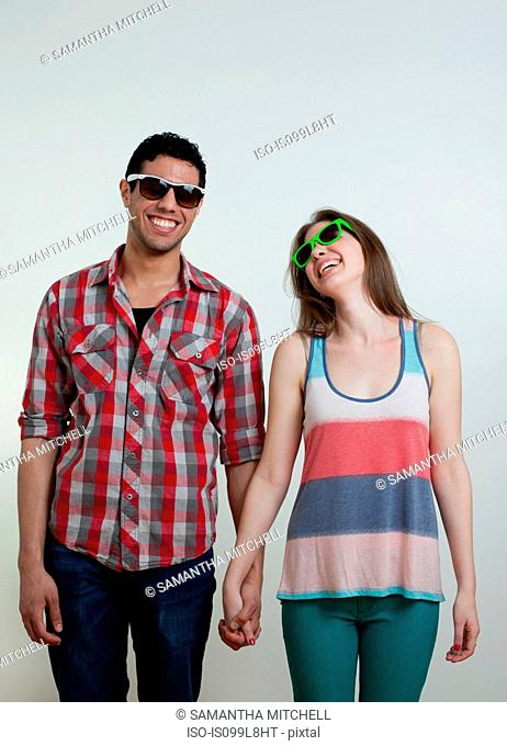 Young couple wearing sunglasses and laughing, studio shot