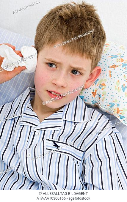 Little boy with ear compress
